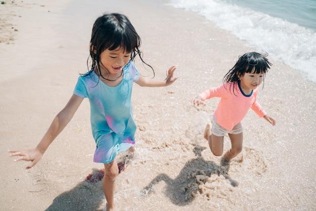 Dwie małe azjatyckie dziewczyny bawiące się na plaży