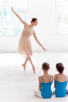 Dwie małe baletnice tańczące z osobistym nauczycielem baletu w studio tańca