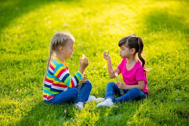 Dwie małe blondynki i brunetka latem siedzą na trawniku dmuchając bańki mydlane dzieci z europy i indii