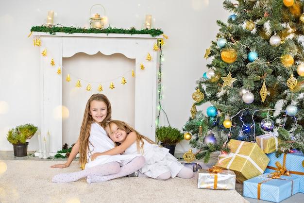 Dwie małe blondynki w białych sukienkach bawią się przy kominku i choince z pudełkami.