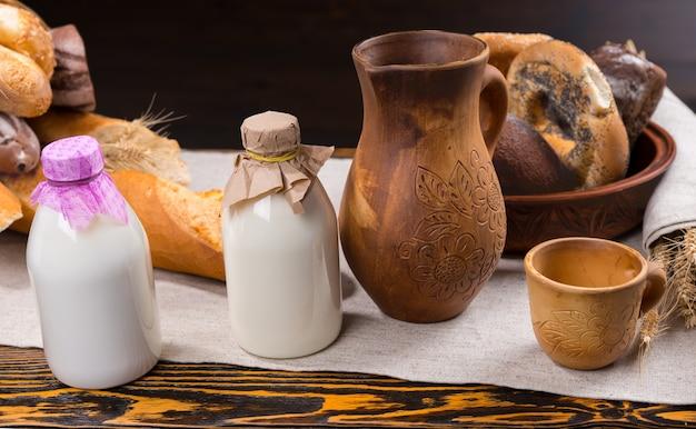 Dwie małe buteleczki mleka z papierowymi przykrywkami obok drewnianego dzbanka, filiżanki i różnych bochenków chleba i bułek na stole
