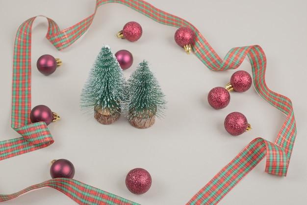 Dwie małe choinki z świąteczną kokardką na białej powierzchni