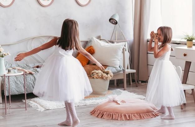 Dwie małe dziewczynki bawią się i tańczą w dużej, oświetlonej sypialni dziecięcej. siostry szczęśliwie spędzają razem czas