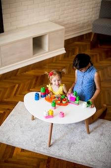 Dwie małe dziewczynki bawią się klockami w pokoju