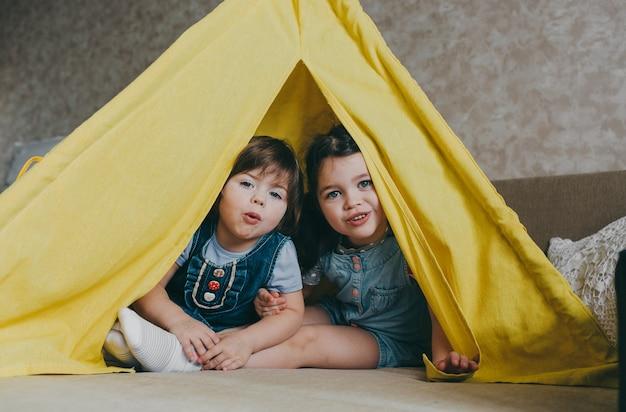 Dwie małe dziewczynki bawią się w domu na żółto w tipi. szczęśliwe dzieciństwo