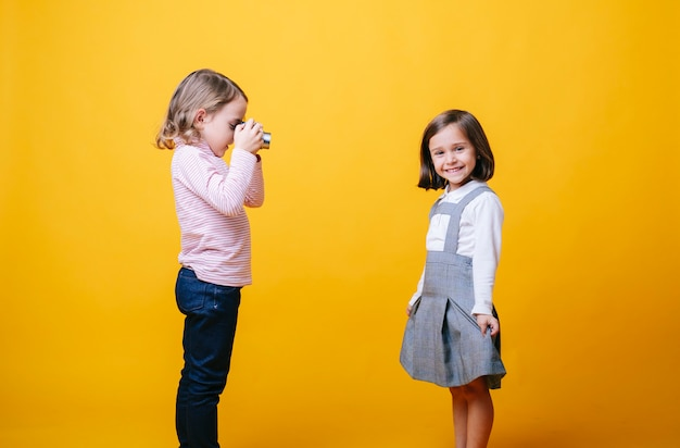 Dwie małe dziewczynki bawiące się aparatem fotograficznym na żółtym tle