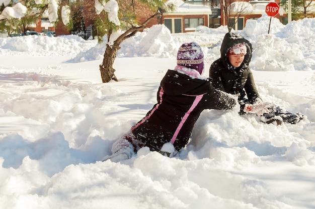Dwie małe dziewczynki bawiące się na śniegu dzieci bawią się zimą śniegiem