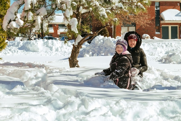 Dwie małe dziewczynki bawiące się na śniegu