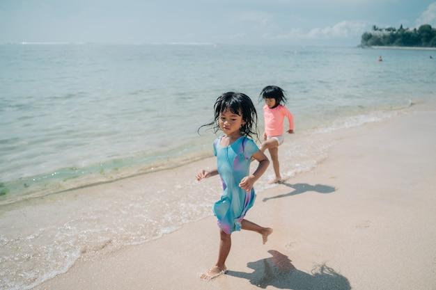 Dwie małe dziewczynki biegną po plaży