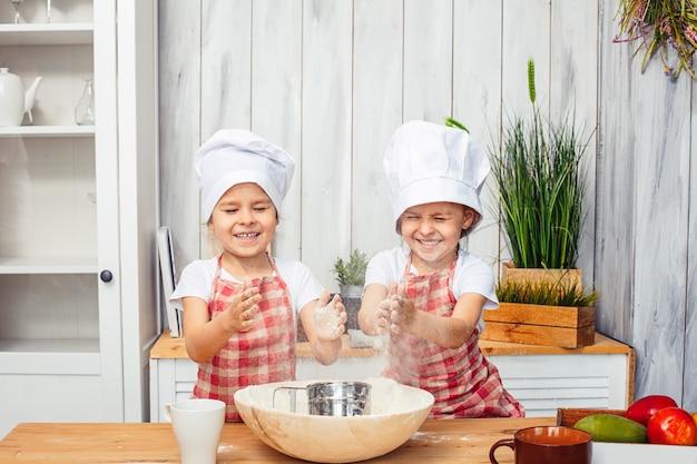 Dwie małe dziewczynki bliźniaczki, siostry bliźniaczki, pieczą w kuchni ciasteczka z mąki.