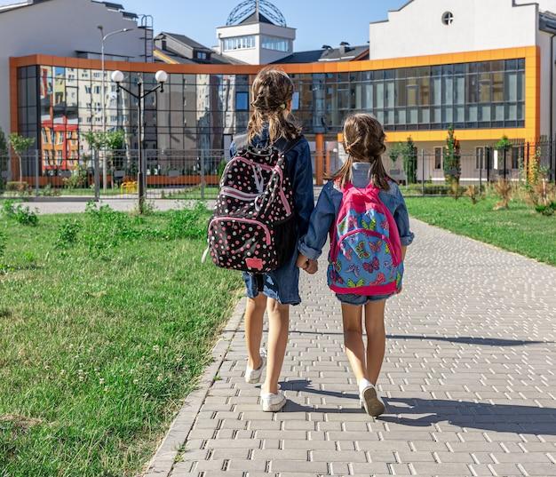 Dwie małe dziewczynki chodzą do szkoły, trzymając się za ręce, widok z tyłu.