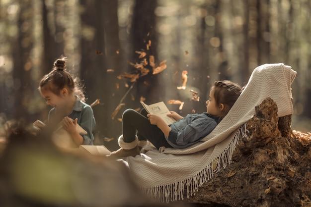 Dwie małe dziewczynki, czytając książki w lesie.