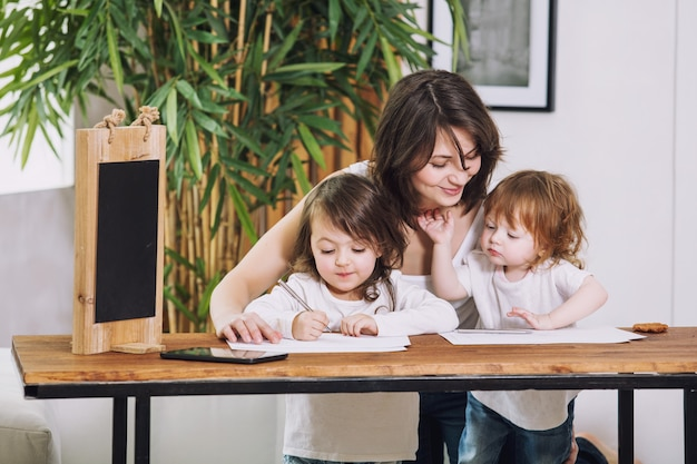 Dwie małe dziewczynki dla dzieci śliczne, piękne i szczęśliwe z mamą w domu, siedzącą przy stole i rysującą