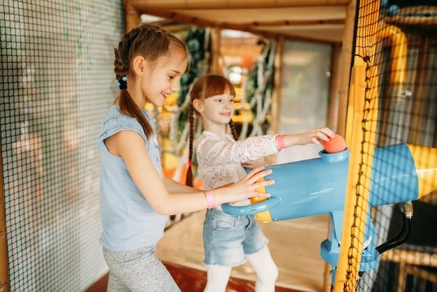 Dwie małe dziewczynki grają w wiatrówkę w centrum gier