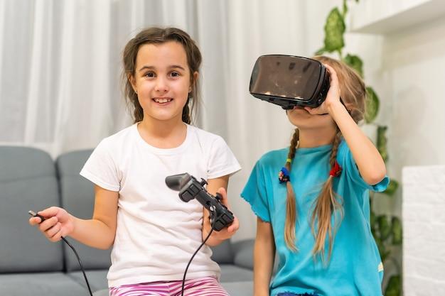 Dwie małe dziewczynki grające w gry wideo okulary wirtualnej rzeczywistości