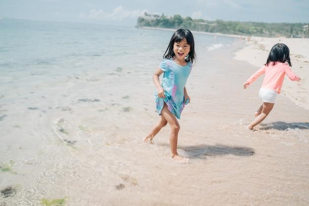 Dwie małe dziewczynki gry w pościg na plaży