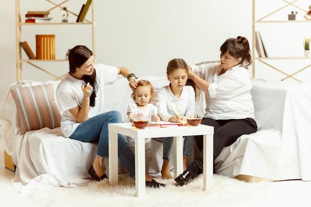 Dwie małe dziewczynki, ich atrakcyjna młoda matka i urocza babcia siedzą na kanapie i spędzają razem czas w domu. pokolenie kobiet. międzynarodowy dzień kobiet. szczęśliwego dnia matki.