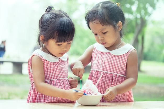 Dwie małe dziewczynki jedzą razem lody
