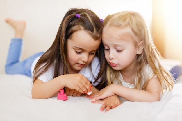 Dwie małe dziewczynki malowały paznokcie w domu