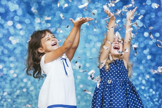 Dwie małe dziewczynki moda dziecięca ze srebrnym konfetti w tle z łatami uroczych