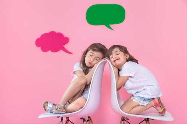 Dwie małe dziewczynki na kolorowej ścianie z ikonami mowy