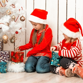 Dwie małe dziewczynki otwierają prezenty świąteczne siedząc na podłodze w pobliżu udekorowanej choinki noworocznej