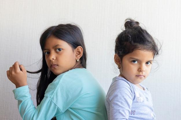 Dwie małe dziewczynki patrzą na siebie