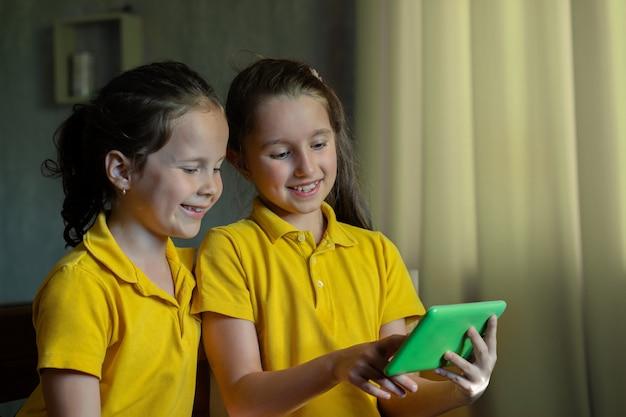 Dwie małe dziewczynki patrzą na tablet i śmieją się