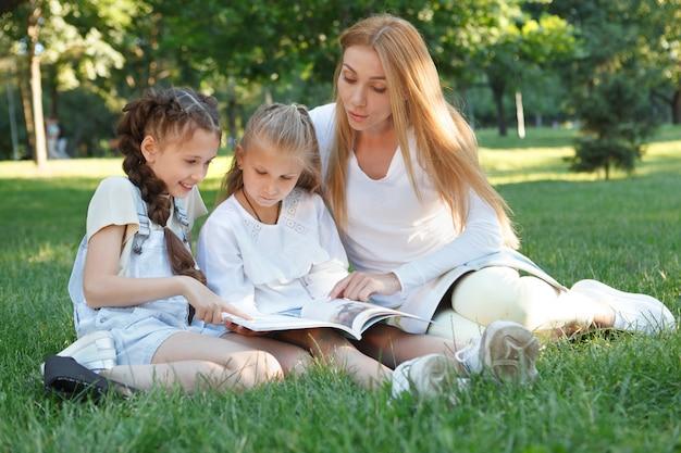 Dwie małe dziewczynki podczas lekcji na świeżym powietrzu w parku ze swoim ulubionym nauczycielem