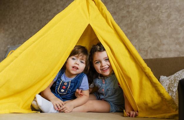 Dwie małe dziewczynki podczas zabawy wyglądają z żółtego tipi w domu. szczęśliwe dzieciństwo
