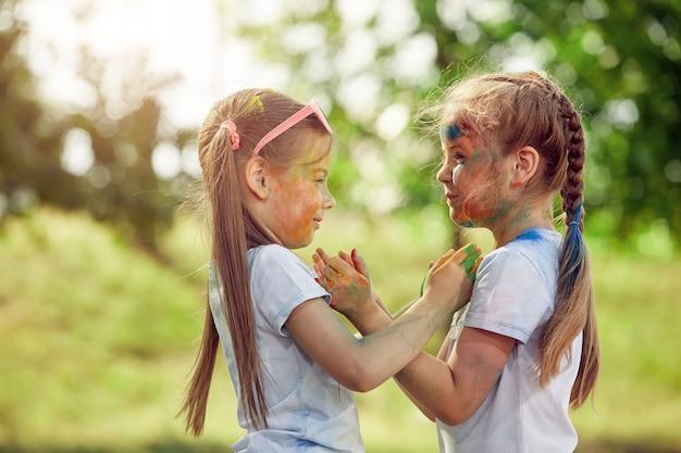Dwie małe dziewczynki poplamione farbami holi bawią się rękami