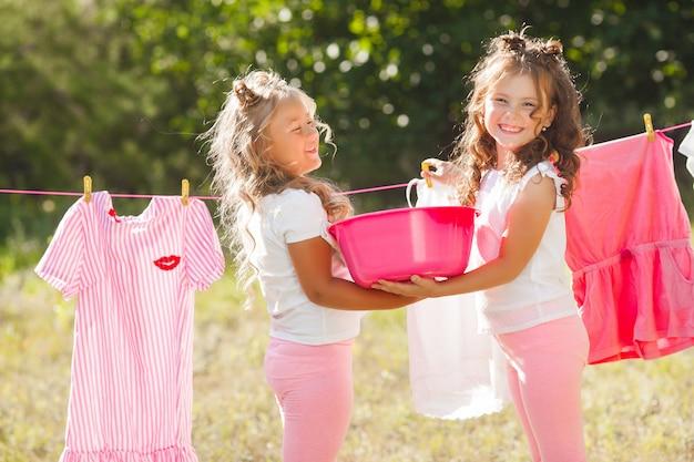 Dwie małe dziewczynki prające. siostry wykonujące prace domowe