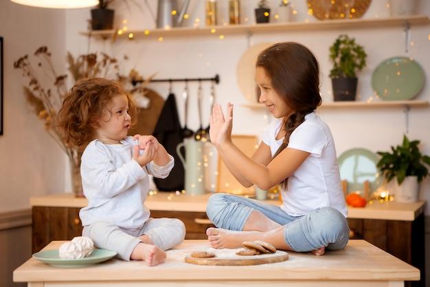 Dwie małe dziewczynki przygotowują w kuchni świąteczne ciasteczka