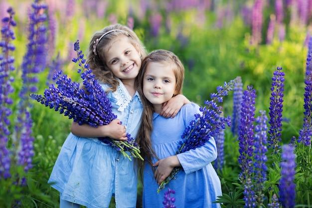 Dwie małe dziewczynki przytulają się i uśmiechają, trzymając w rękach kwiaty w polu fioletowych kwiatów