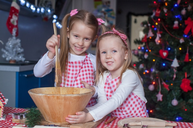 Dwie małe dziewczynki robią piernikowe ciasteczka na boże narodzenie