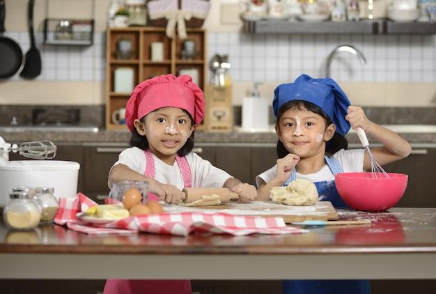 Dwie małe dziewczynki robią pizzę