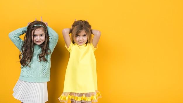 Dwie małe dziewczynki robią rogi palcami