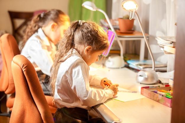 Dwie małe dziewczynki rysujące obrazki za biurkiem
