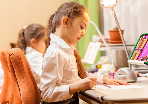 Dwie małe dziewczynki rysujące obrazki