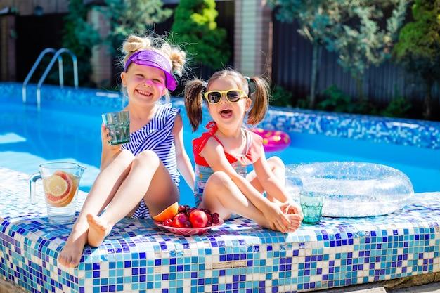 Dwie małe dziewczynki siedzą latem przy basenie w okularach przeciwsłonecznych i piją lemoniadę