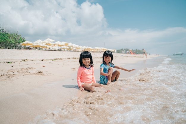 Dwie małe dziewczynki siedzą na piasku i czekają na nadchodzące fale