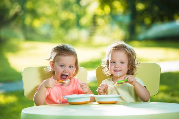 Dwie małe dziewczynki siedzą przy stole i jedzą razem na zielonym trawniku