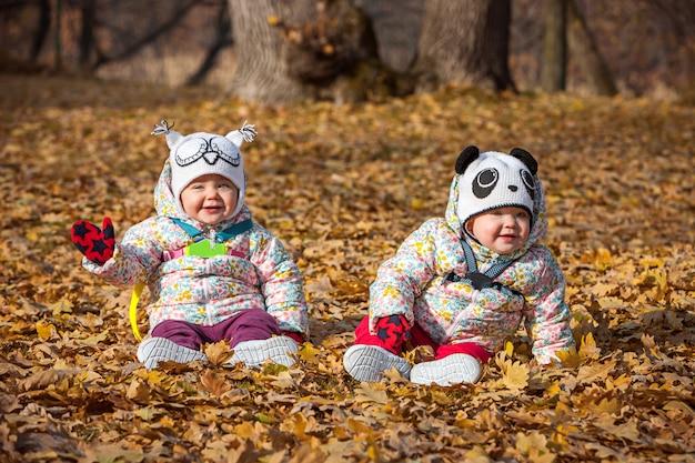 Dwie małe dziewczynki siedzące na jesiennych liściach