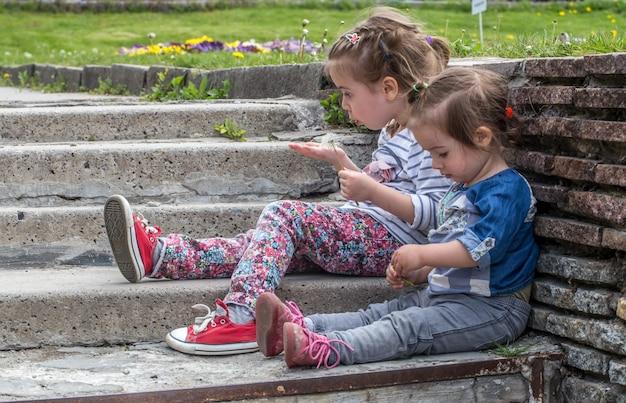 Dwie małe dziewczynki siedzące na schodach na zewnątrz, koncepcja odpoczynku dzieci