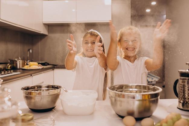 Dwie małe dziewczynki siostry, gotowanie w kuchni