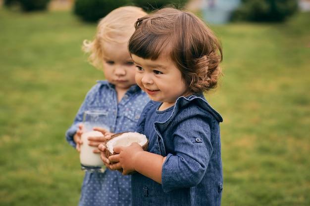 Dwie małe dziewczynki trzymające w rękach szklankę mleka kokosowego i kokosa. zdrowe i zdrowe jedzenie.