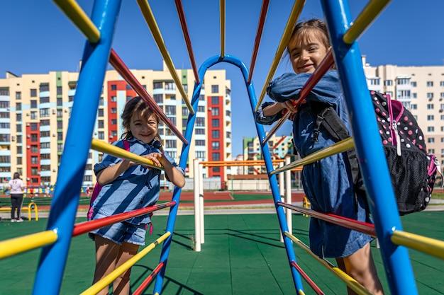 Dwie małe dziewczynki, uczennice szkoły podstawowej, po szkole bawią się na boisku.