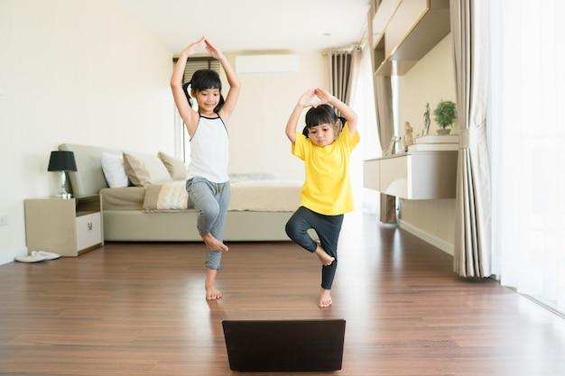 Dwie małe dziewczynki uprawiania jogi, rozciąganie, fitness przez wideo na notebooku.