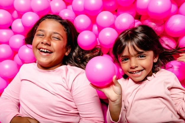 Dwie małe dziewczynki uśmiechnięte i grając w różowy basen z piłeczkami