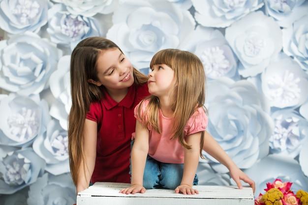 Dwie małe dziewczynki uśmiechnięte i patrząc na siebie